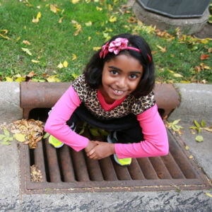 Girl sitting on storm drain