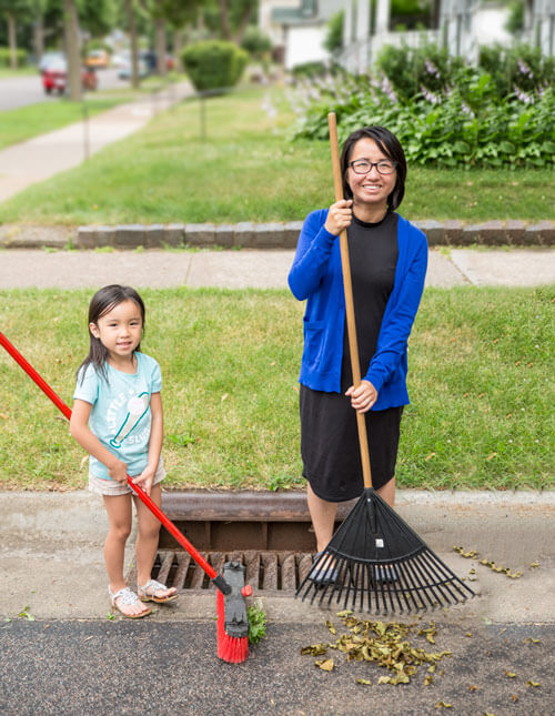Mother and child sweeping storm drain