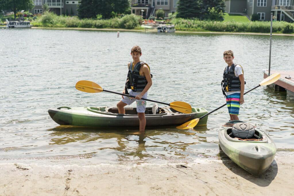 Boys with kayaks on lake