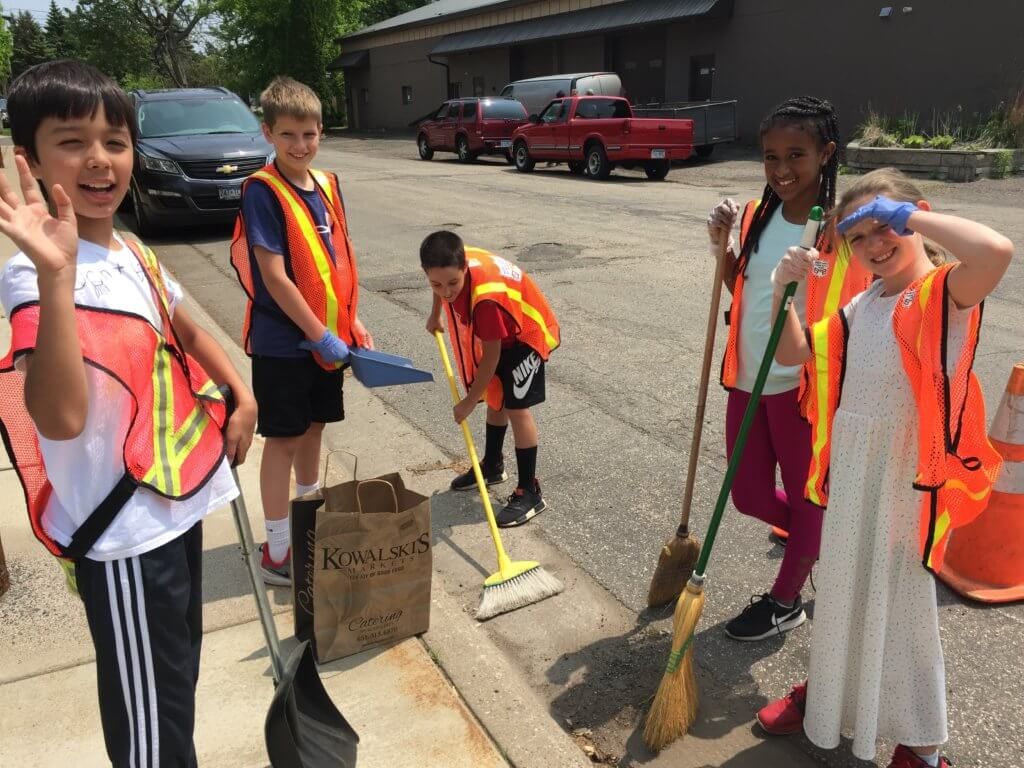 Kids cleaning a storm drain.