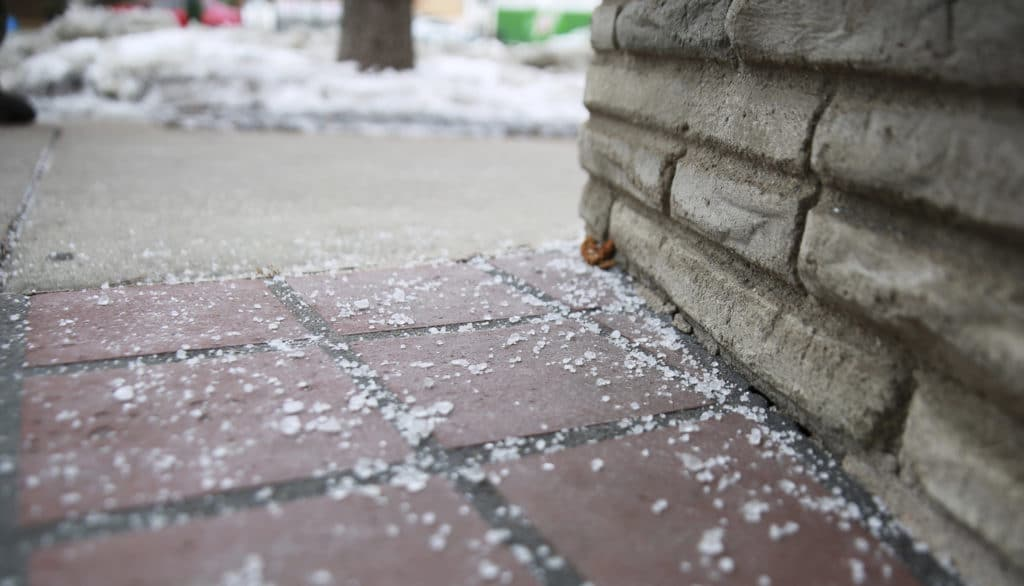 Road salt that remains after the ice has melted is a sign of over-salting.